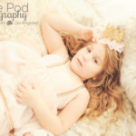 beautiful-child-photographer-brentwood-laying-on-bed-crown-pink-gold-dress