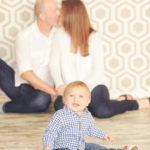 Best-Family-Photographer-Brentwood-Studio-Portrait-Session-Focus-On-Baby-Parents-Kissing-In-Background