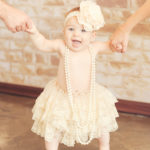 Baby-Girl-Standing-Holding-Mom-And-Dad-Hands-Lace-Tutu-Headband-Pearls-Best-Photography-Studio-Los-Angeles