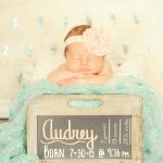 baby girl sleeping in a chalkboard box with her birth information written on it