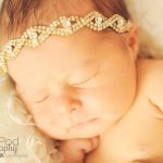 close up of newborn baby girl wearing a gold diamond headband