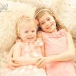 two sisters laying on a bed holding hands and looking at the camera, wearing all pink