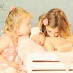 two sisters kissing newborn baby girl los angeles photographer