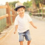boy with hat at the venice canals running candid photo