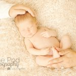newborn baby on beige fur fabric with parents holding him photo