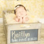 baby holdin gher head in her hands sleeping in a chalkboard bod with her name on it