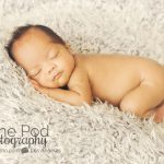 infant-snuggled-on-gray-fabric