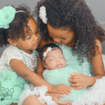 sisters-kissing-new-baby
