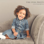 two-year-old-baby-girl-sitting-on-chaise-lounge