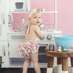 one-year-old-baby-girl-playing-in-kitchen-over-the-shoulder-look
